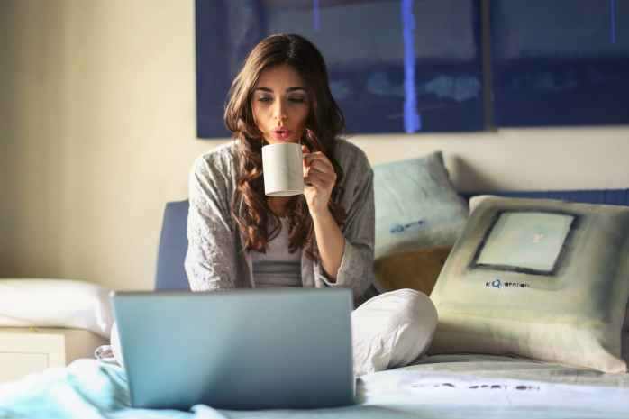 woman in grey jacket sits on bed uses grey laptop